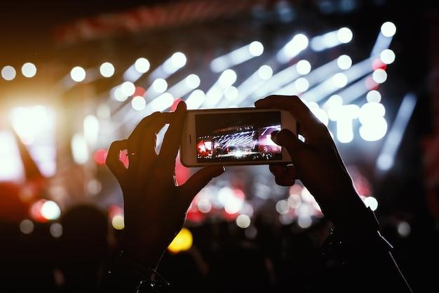Mãos com smartphone gravam festival de música ao vivo