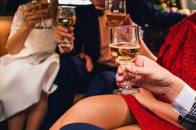 Mãos com taças de champanhe comemorando casamento