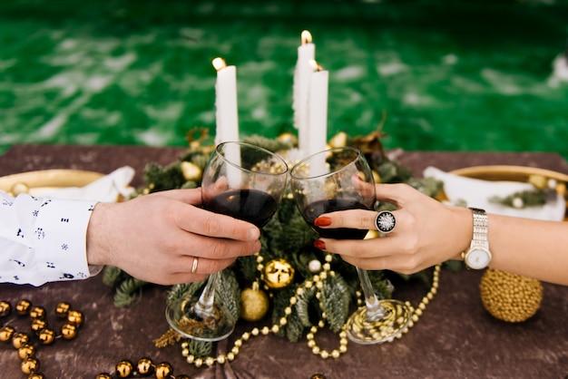 Mãos com taças de vinho em uma mesa de férias muito bem servido. natal