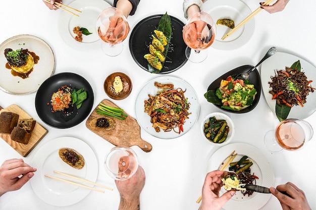 Mãos com taças de vinho rosé para jantar familiar em estilo asiático