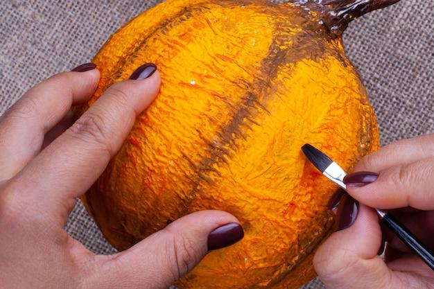 Mãos com tinta de manicure escura com um pincel com guache laranja cores abóbora artesanal de papel machê para o halloween