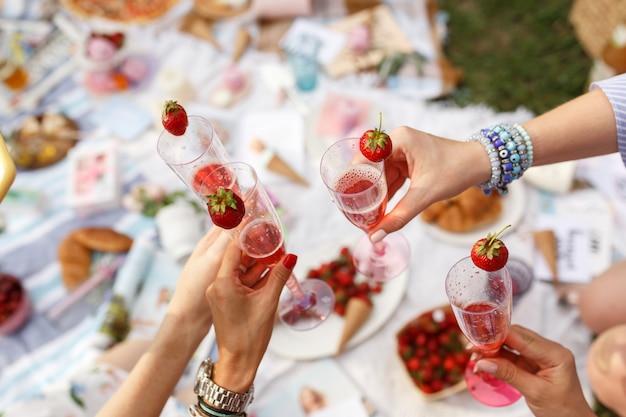 Mãos com um brinde de óculos no piquenique de dia de verão.