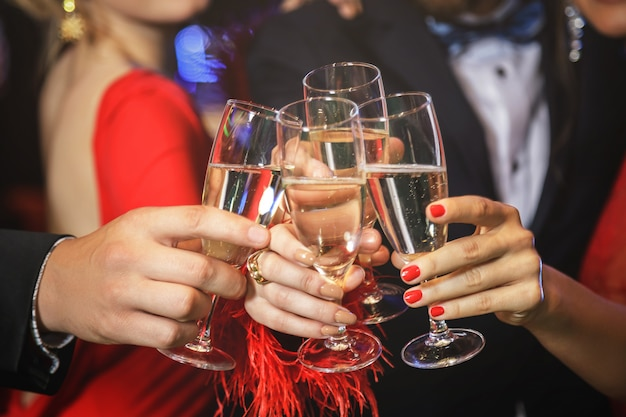 Mãos com um copo cheio de vinho espumante