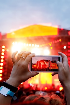 Mãos com um smartphone gravam festival de música ao vivo, concerto ao vivo, concerto ao vivo.