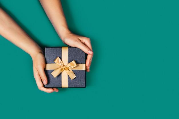 Mãos com uma caixa de presente.