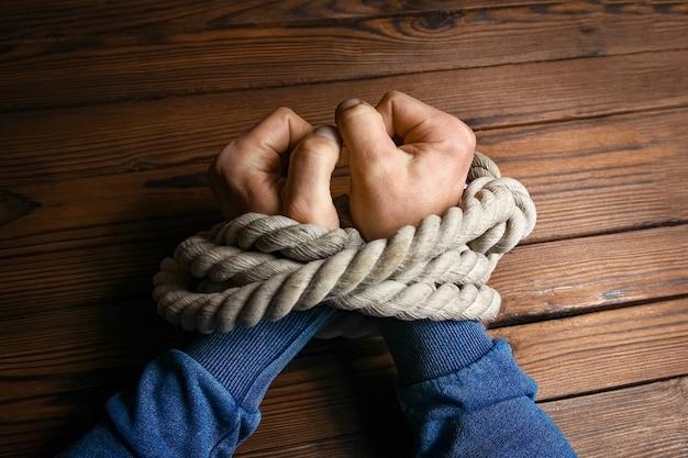 Mãos com uma corda em um fundo de madeira