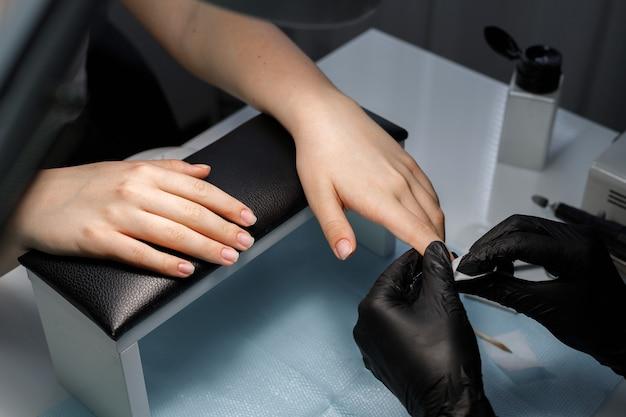 Mãos com uma manicure no salão de beleza. o trabalho de uma manicure mestre
