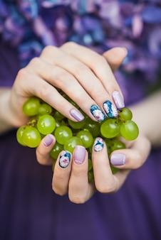 Mãos com unhas segurando uvas