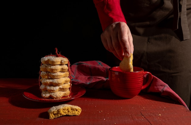 Mãos, conjunto de biscoitos, xícara de café ou chá vermelho na mesa de madeira vermelha no preto.