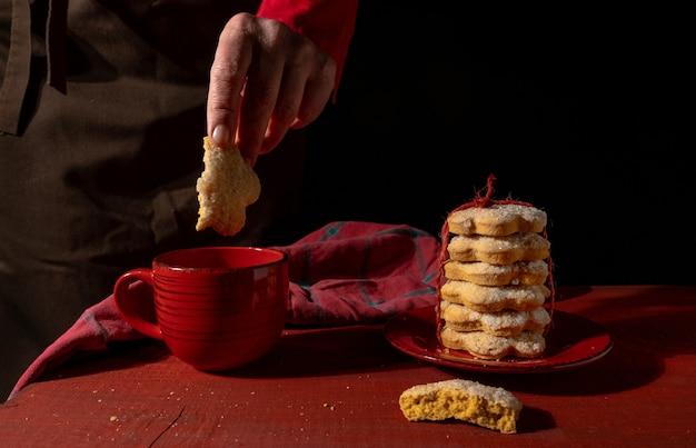 Mãos, conjunto de biscoitos, xícara de café vermelha ou chá na mesa de madeira vermelha