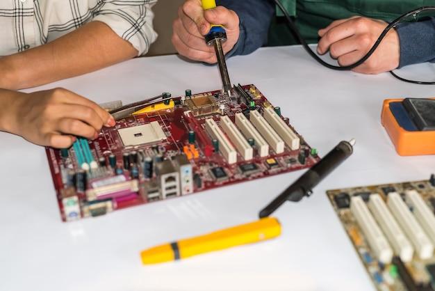 Mãos consertando placa-mãe de computador por soldagem de perto