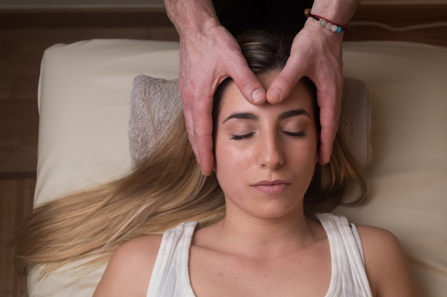 Mãos cortadas de terapeuta realizando reiki em mulher