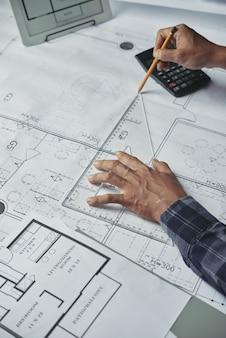 Mãos cortadas do arquiteto blueprinting para o projeto arquitetônico
