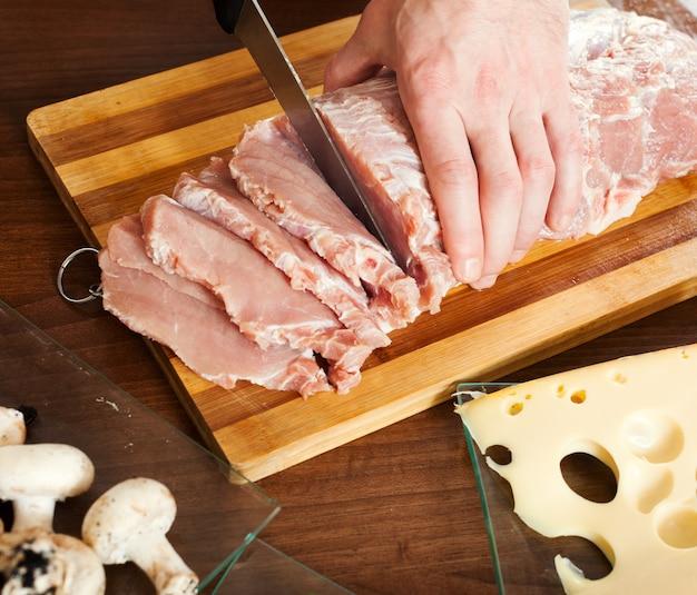 Mãos cortando carne crua