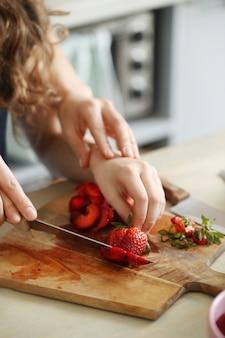 Mãos cortando morangos frescos