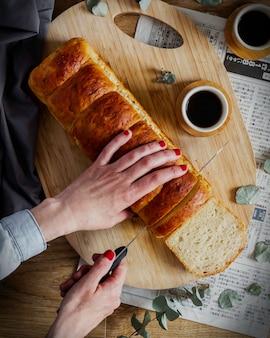 Mãos cortando pão de leite caseiro