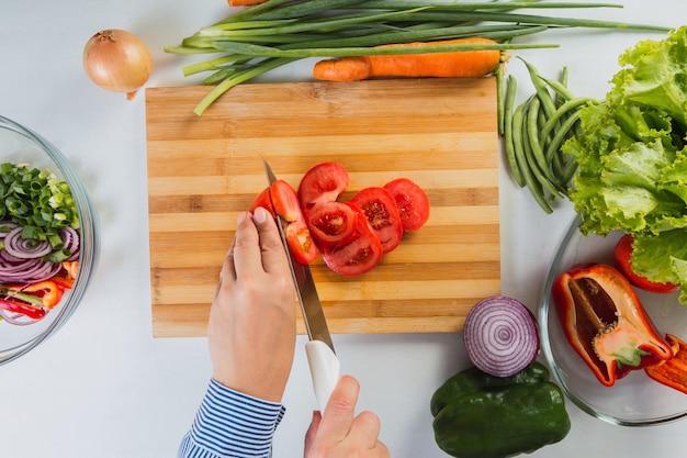 Mãos cortando tomates frescos e maduros em uma mesa de madeira.