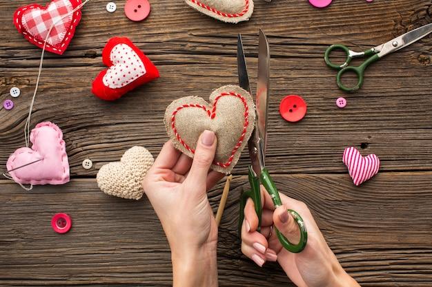Mãos cortando uma forma de coração vermelho sobre fundo de madeira
