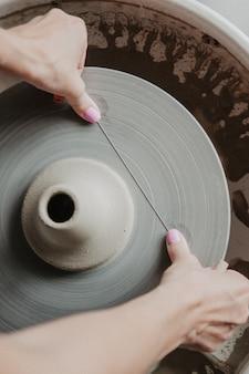 Mãos cortando vaso de barro com arame