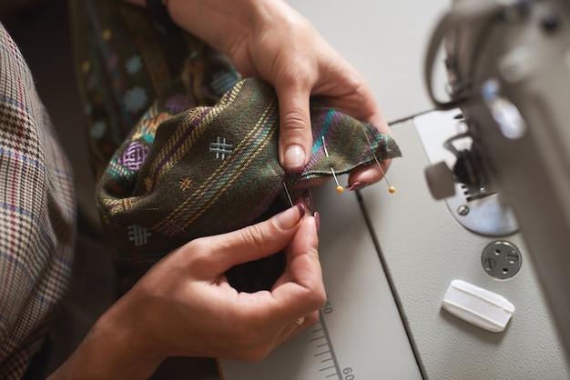 Mãos costurando detalhes de roupas na máquina de costura elétrica
