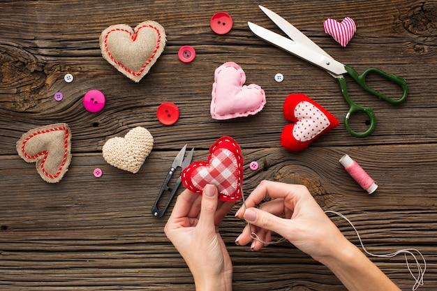 Mãos costurando uma forma de coração vermelho sobre fundo de madeira