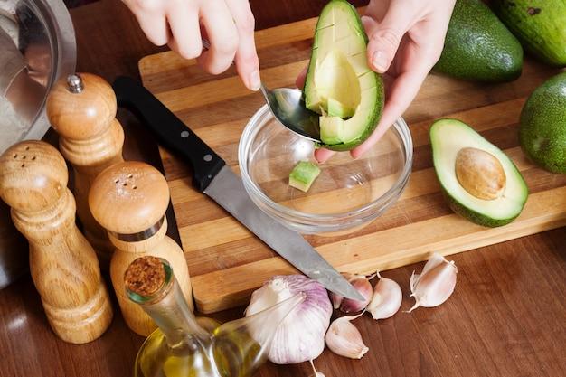 Mãos cozinhando com abacate