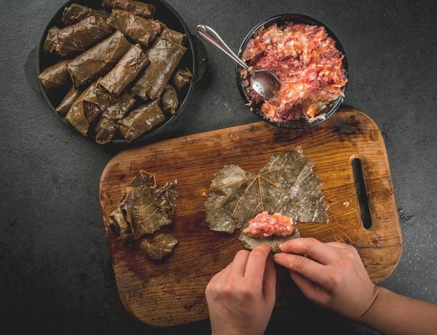 Mãos cozinhar dolma na mesa de corte de madeira