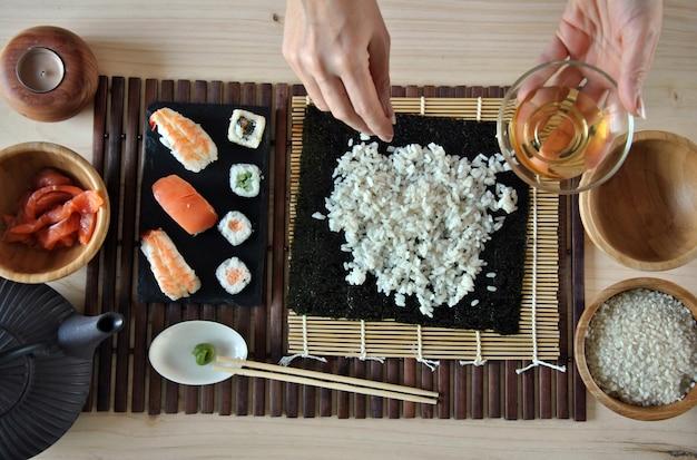 Mãos cozinhar sushi com arroz, salmão e nori