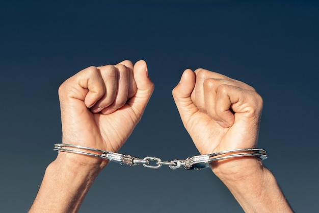 Mãos criminosas trancadas em algemas. vista de perto
