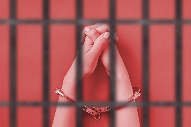 Mãos cruzadas algemadas, atrás das grades. conceito de prisão perpétua. privação de liberdade e captura de perpetradores.