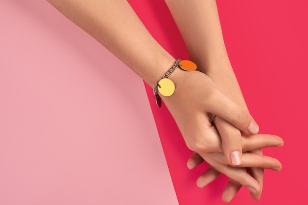 Mãos cruzadas de uma jovem desconhecida em uma pulseira de prata ou platina brilhante
