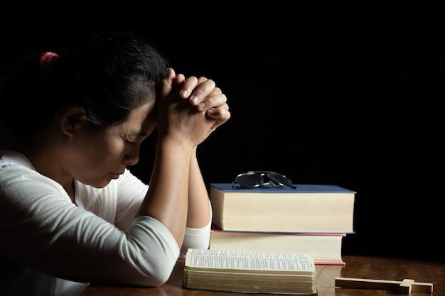 Mãos cruzadas em oração na bíblia sagrada na igreja