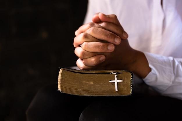 Mãos cruzadas em oração na bíblia sagrada no conceito de igreja pela fé