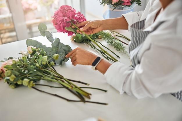 Mãos cuidadosas de uma florista arrumando as flores em uma composição