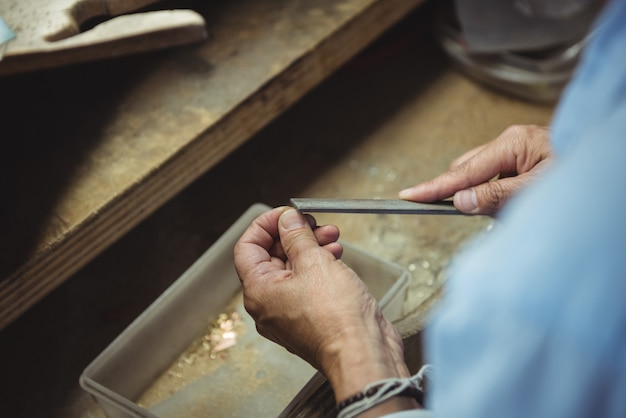 Mãos da artesã usando a ferramenta