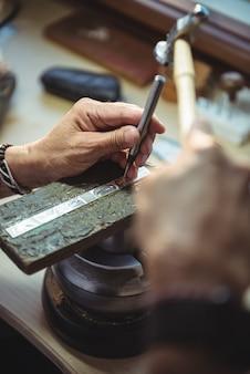 Mãos da artesã usando ferramentas