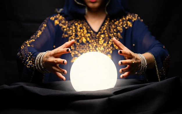 Mãos da cartomante com bola de cristal