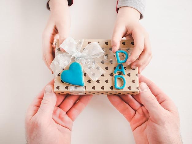 Mãos da criança e uma linda caixa de presente