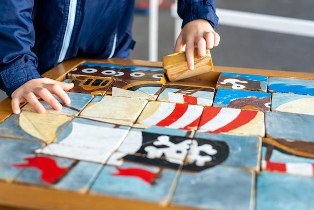 Mãos da criança que terminam um enigma do artesão feito de cubos de madeira.