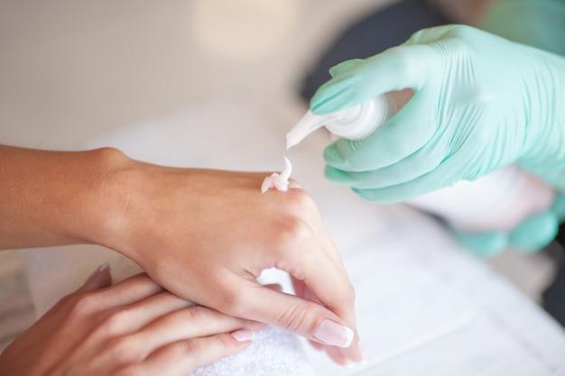 Mãos da desinfecção antes do tratamento de mãos no close up do salão de beleza. esteticista está desinfetando o cliente com desinfetante