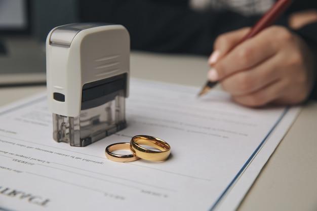 Mãos da esposa, marido assinando decreto de divórcio, dissolução, cancelamento de casamento, documentos de separação judicial
