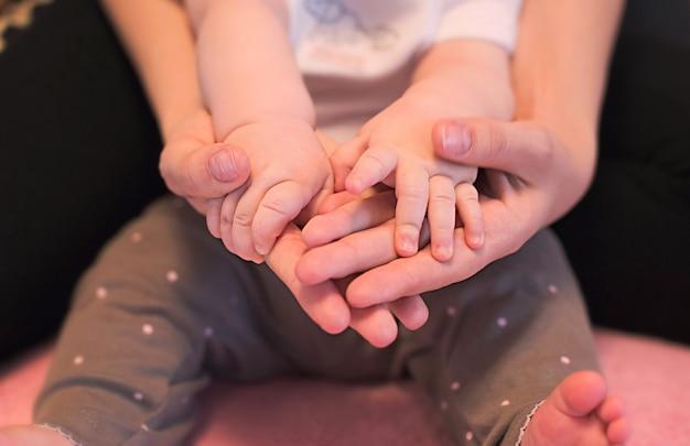 Mãos da família incompleta, pai ou mãe e filho