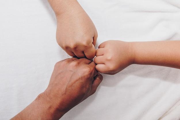 Mãos da família, um bebê, uma filha, uma mãe e um pai.