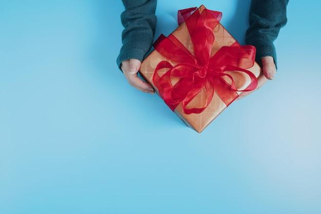 Mãos da fêmea segurando uma caixa de presente com fita vermelha no azul