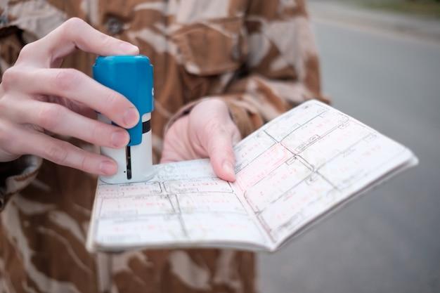 Mãos da guarda de fronteira feminina; carimbo de passaporte durante o controle de fronteira