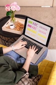 Mãos da jovem designer feminina no teclado do laptop durante o trabalho criativo no ambiente doméstico, por uma pequena mesa com lanche, bebida e rosas