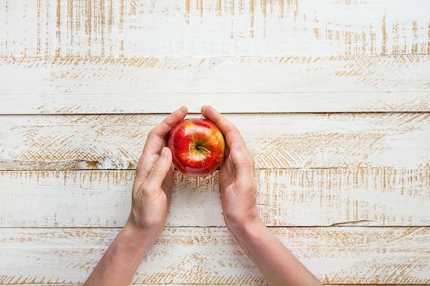 Mãos da jovem mulher que guardam apple vermelho maduro na tabela branca da madeira da prancha. ação de graças