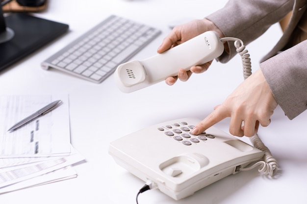 Mãos da jovem secretária do escritório discando o número de telefone e segurando o fone enquanto liga para um dos clientes no local de trabalho