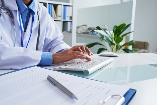 Mãos da médica irreconhecível digitando no teclado no escritório