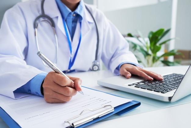 Mãos da médica irreconhecível, escrevendo no formulário e digitando no teclado do laptop